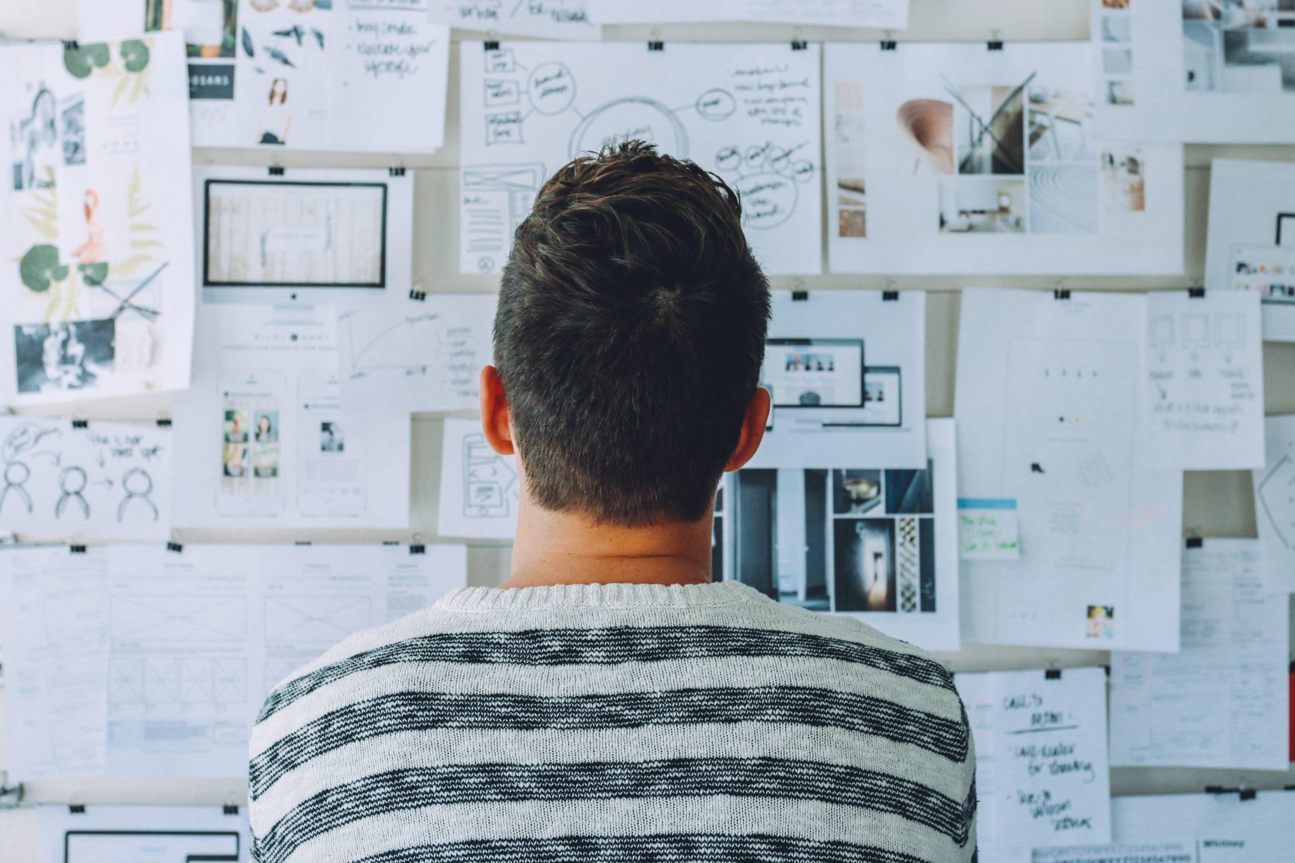 Männliche Person betrachtet Dokumente an Wand.